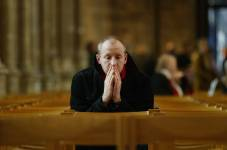 A picture of a man in church doing one of possibly many types of prayer